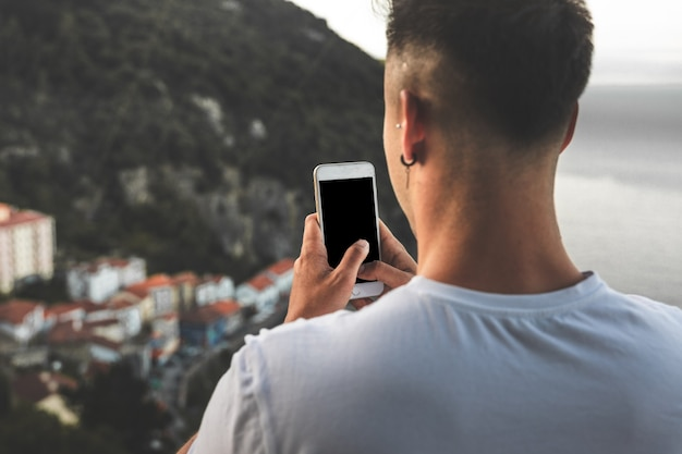 Jonge blanke man die een foto maakt met een mobiele telefoon vanuit een hoog uitzicht op een klein kustplaatsje