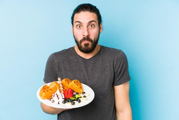 Jonge blanke man die een geïsoleerd wafel dessert eet haalt zijn schouders op en opent verwarde ogen.