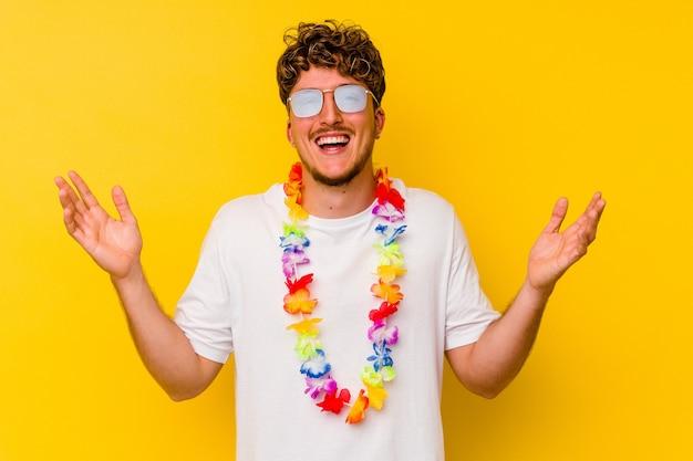 Jonge blanke man die een hawaiiaans feestspullen draagt ?? die op gele achtergrond wordt geïsoleerd en een aangename verrassing ontvangt, opgewonden en handen opheft.