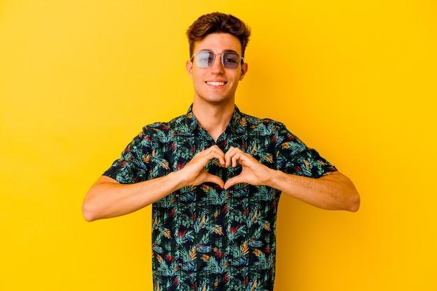 Jonge blanke man die een hawaiiaans shirt draagt dat op gele muur wordt geïsoleerd die en een hartvorm met handen glimlacht toont.
