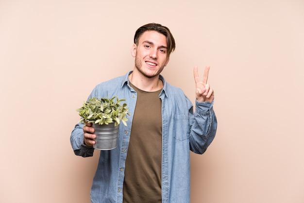 Jonge blanke man die een plant blij en zorgeloos houdt met een vredessymbool met vingers.