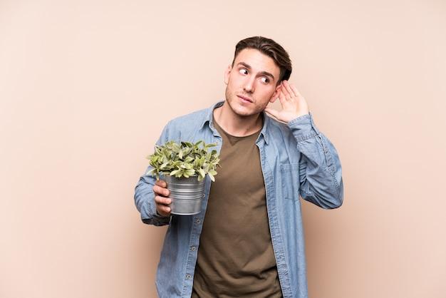 Jonge blanke man die een plant houdt die probeert een roddel te luisteren.