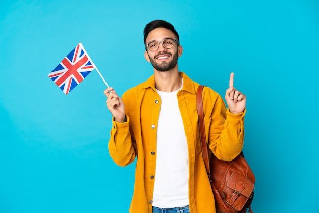 Jonge blanke man die een vlag van het verenigd koninkrijk houdt die op gele muur wordt geïsoleerd die en een vinger opheft als teken van het beste