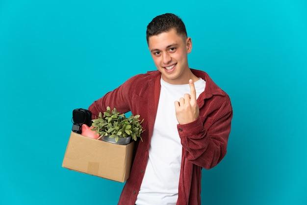 Jonge blanke man die een zet doet terwijl hij een doos vol dingen oppakt die op blauw worden geïsoleerd en komend gebaar doen