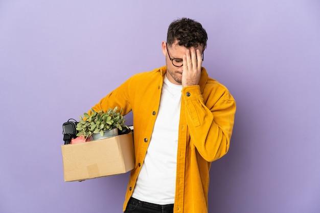 Jonge blanke man die een zet doet terwijl hij een doos vol dingen oppakt die op paarse achtergrond worden geïsoleerd met een vermoeide en zieke uitdrukking