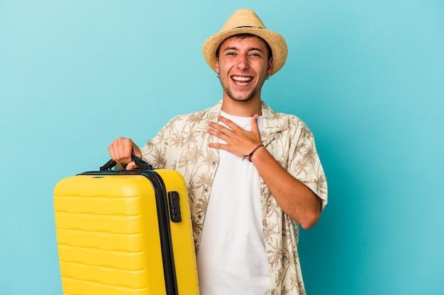Jonge blanke man die geïsoleerd op een blauwe achtergrond gaat reizen, lacht hardop terwijl hij de hand op de borst houdt.