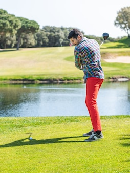 Jonge blanke man die golf speelt op een professionele golfbaan
