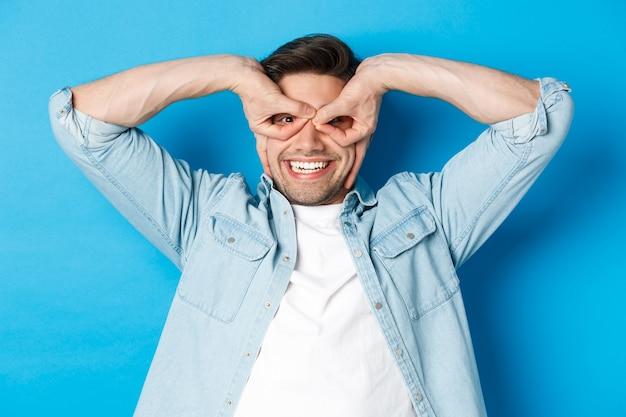 Jonge blanke man die grappige uitdrukking toont, een superheldenmasker maakt met vingers op de ogen, gelukkig lacht, over een blauwe achtergrond staat
