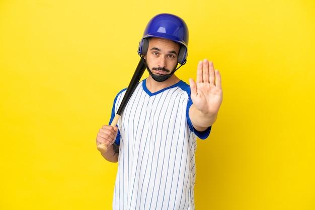 Jonge blanke man die honkbal speelt geïsoleerd op een gele achtergrond die een stopgebaar maakt