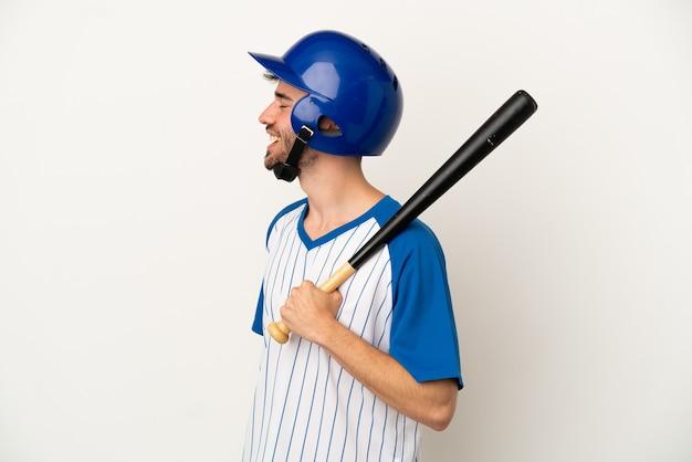 Jonge blanke man die honkbal speelt geïsoleerd op een witte achtergrond lachend in zijpositie