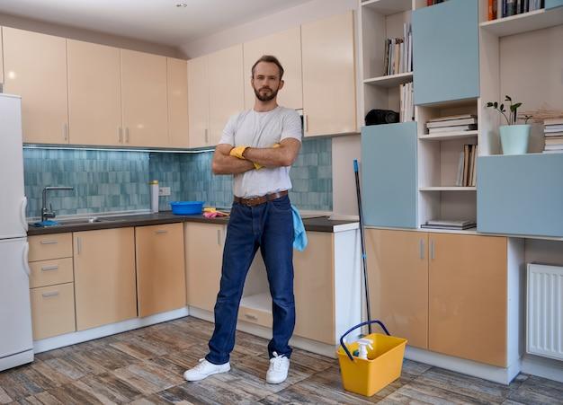 Jonge blanke man die met gekruiste handen in de keuken staat