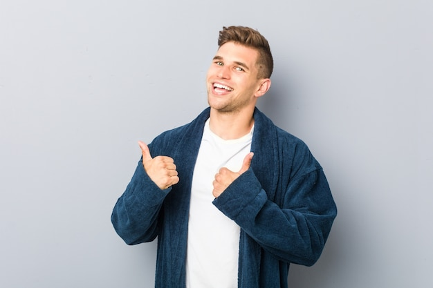 Jonge blanke man die pyjama draagt en beide duimen opheft, glimlachend en zelfverzekerd.