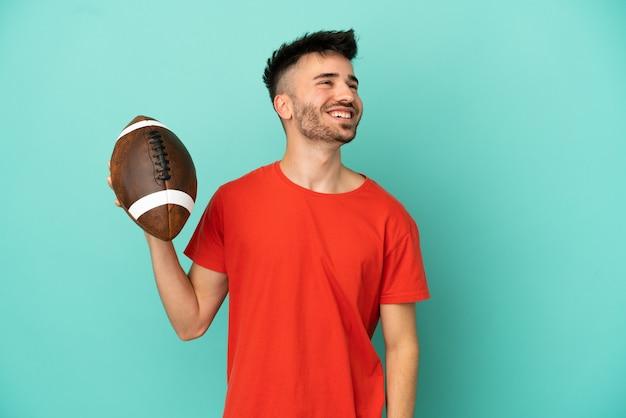 Jonge blanke man die rugby speelt geïsoleerd op een blauwe achtergrond en een idee denkt terwijl hij omhoog kijkt