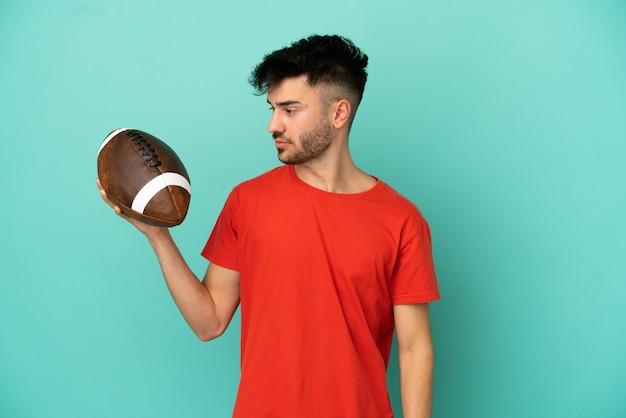 Jonge blanke man die rugby speelt geïsoleerd op een blauwe achtergrond en naar de zijkant kijkt