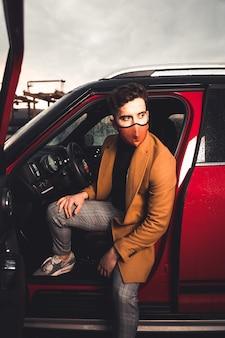 Jonge blanke man die uit een rode auto gaat met een masker op een parkeerplaats.