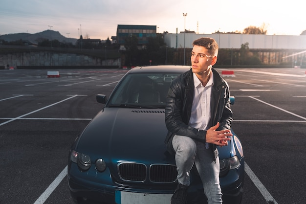 Jonge blanke man die zich voordeed op een parkeerplaats met een sportwagen