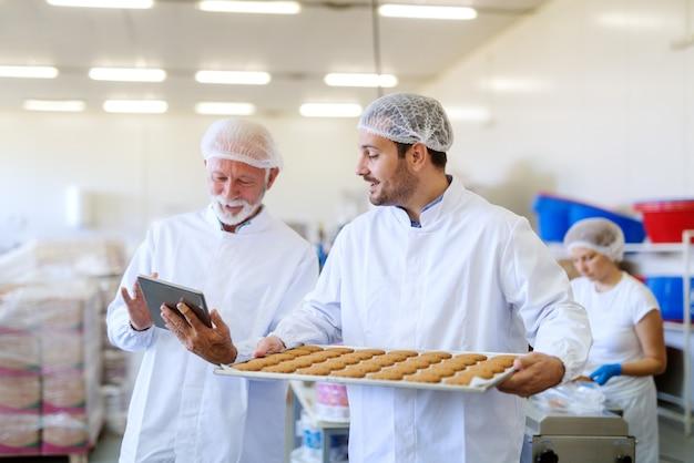 Jonge blanke man dienblad met koekjes te houden en te praten met oudere collega die hem salaris op tablet toont.