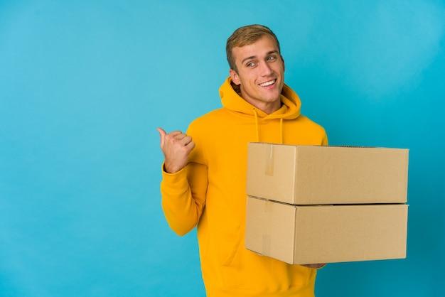 Jonge blanke man doet verhuizen geïsoleerd, wijst met duimvinger weg, lachen en zorgeloos.
