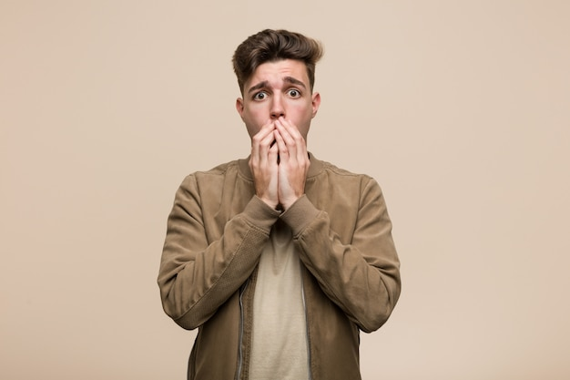 Jonge blanke man draagt een bruin jasje bang en bang.