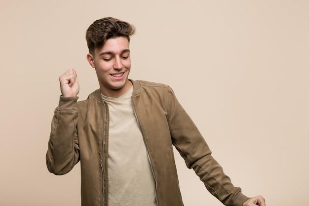 Jonge blanke man draagt een bruine jas dansen en plezier.