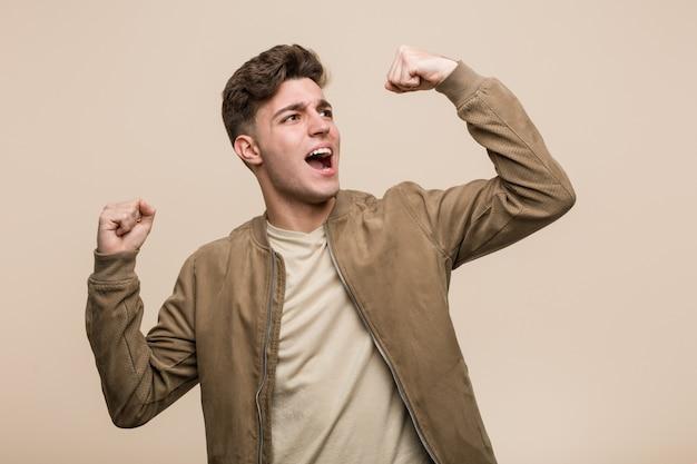 Jonge blanke man draagt een bruine jas verhogen vuist na een overwinning