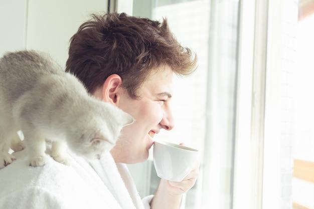 Jonge blanke man drinkt koffie bij het raam. hij houdt een kat vast en glimlacht. vroege ochtend, zonneschijn.