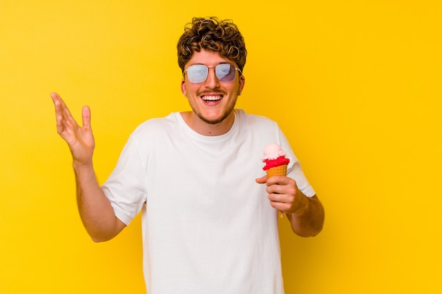 Jonge blanke man eet een ijsje geïsoleerd op gele achtergrond en ontvangt een aangename verrassing, opgewonden en handen opsteken.
