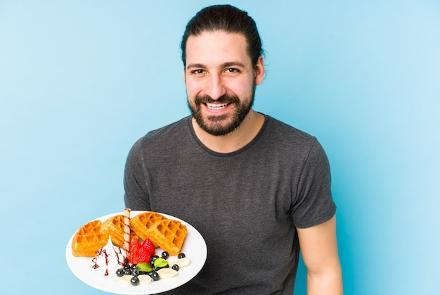 Jonge blanke man eet een wafel dessert geïsoleerd lachen en plezier maken.