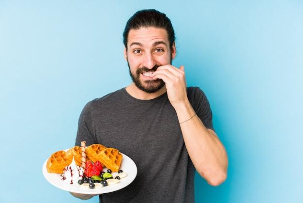 Jonge blanke man eet een wafel dessert geïsoleerd vingernagels bijten, nerveus en erg angstig.