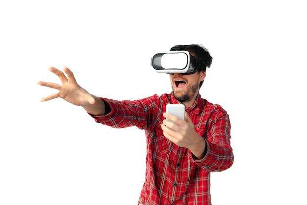Jonge blanke man emotioneel spelen, met behulp van virtual reality headset en smartphone geïsoleerd op een witte studio muur. concept van moderne technologieën, gadgets, tech, menselijke emoties, advertentie. kopieerruimte.