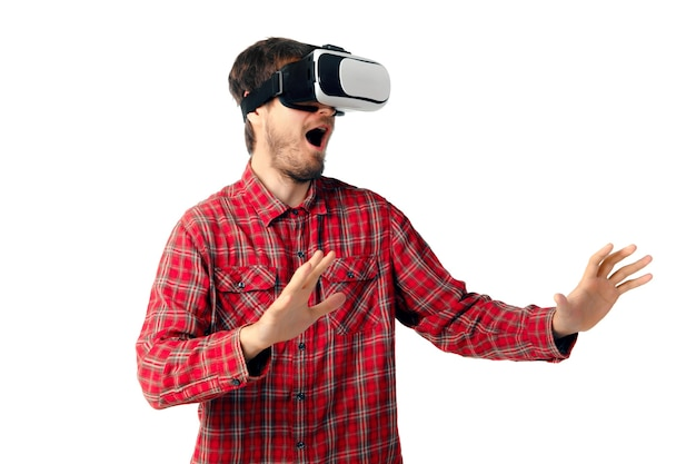 Jonge blanke man emotioneel spelen, met behulp van virtual reality headset geïsoleerd op witte studio muur. concept van moderne technologieën, gadgets, tech, menselijke emoties, reclame. kopieerruimte. ar, vr.