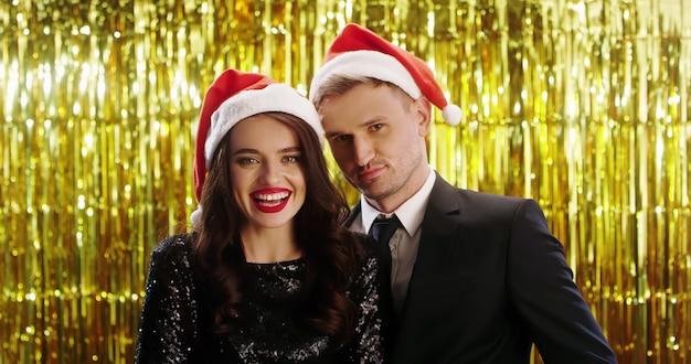 Jonge blanke man en vrouw in santa claus-hoeden