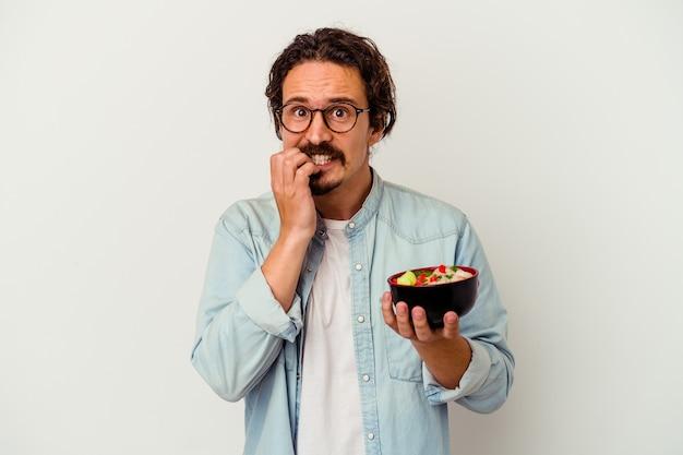 Jonge blanke man eten ramen geïsoleerd op wit vingernagels bijten, nerveus en erg angstig.
