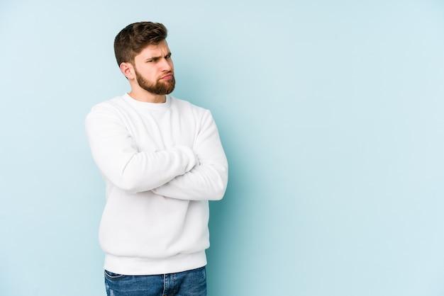 Jonge blanke man fronsend gezicht in ongenoegen, houdt armen gevouwen.