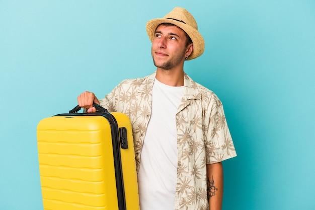 Jonge blanke man gaat reizen geïsoleerd op blauwe achtergrond dromen van het bereiken van doelen en doeleinden
