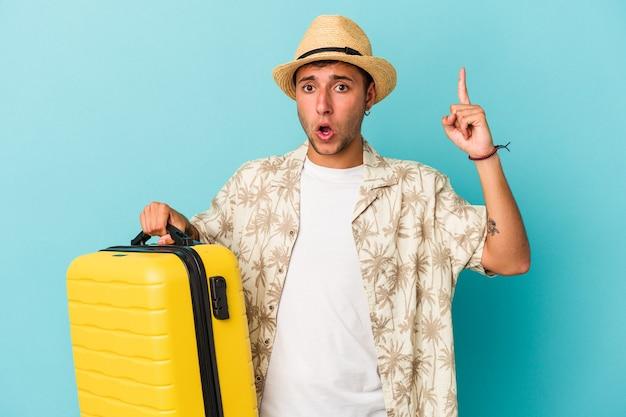 Jonge blanke man gaat reizen geïsoleerd op blauwe achtergrond met een idee, inspiratie concept.