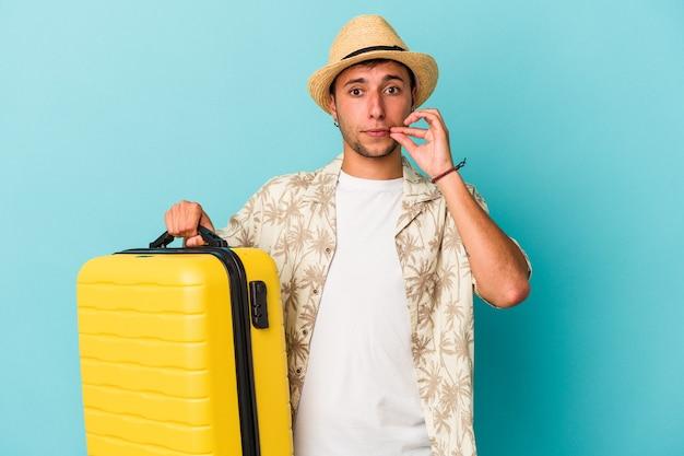Jonge blanke man gaat reizen geïsoleerd op blauwe achtergrond met vingers op lippen die een geheim houden.