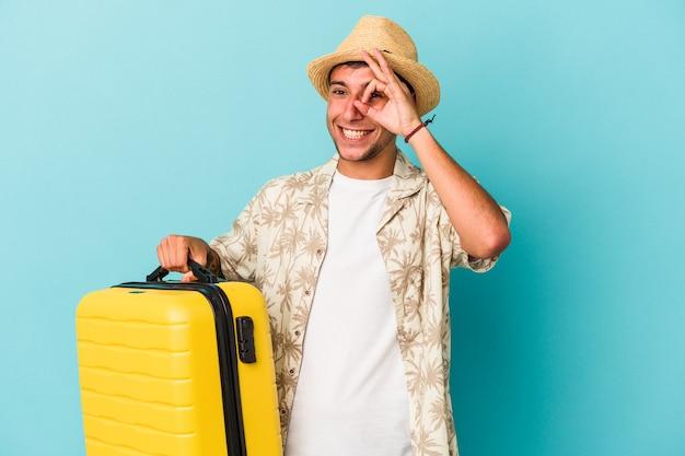 Jonge blanke man gaat reizen geïsoleerd op blauwe achtergrond opgewonden houden ok gebaar in de gaten.