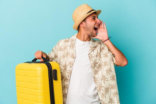 Jonge blanke man gaat reizen geïsoleerd op blauwe achtergrond schreeuwen en houden palm in de buurt van geopende mond.