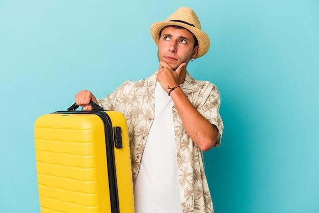 Jonge blanke man gaat reizen geïsoleerd op blauwe achtergrond zijwaarts kijkend met twijfelachtige en sceptische uitdrukking.