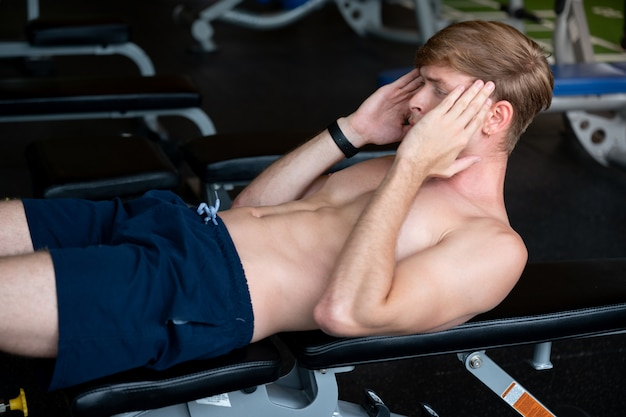 Jonge blanke man gaat zitten en gewichtheffen in de fitnessruimte