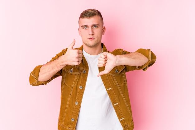Jonge blanke man geïsoleerd duimen opdagen en duimen naar beneden, moeilijk kiezen concept
