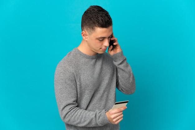 Jonge blanke man geïsoleerd kopen met de mobiele telefoon met een creditcard