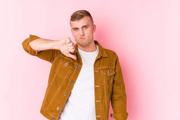 Jonge blanke man geïsoleerd met een afkeer gebaar, duimen naar beneden. meningsverschil concept.