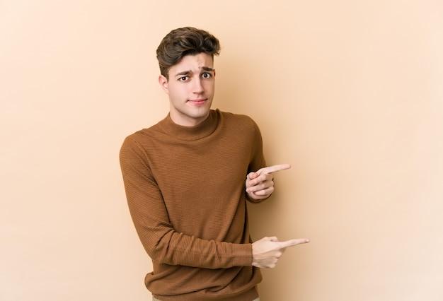 Jonge blanke man geïsoleerd op beige muur geschokt wijzend met wijsvingers naar een kopie ruimte.