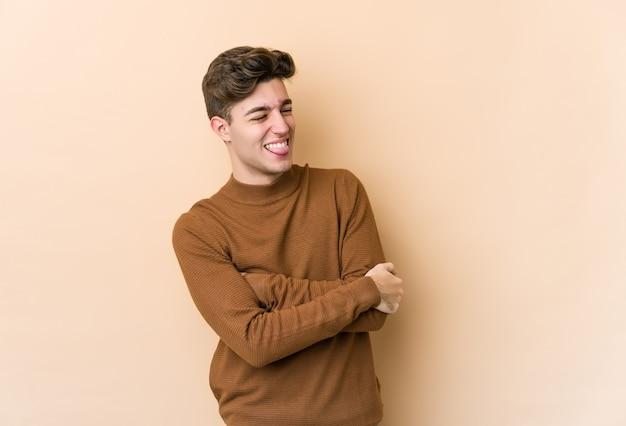 Jonge blanke man geïsoleerd op beige muur grappige en vriendelijke tong uitsteekt.
