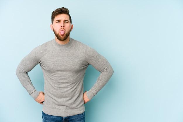 Jonge blanke man geïsoleerd op blauw grappige en vriendelijke tong uitsteekt.