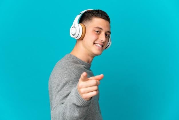 Jonge blanke man geïsoleerd op blauw luisteren muziek en wijst naar de voorkant