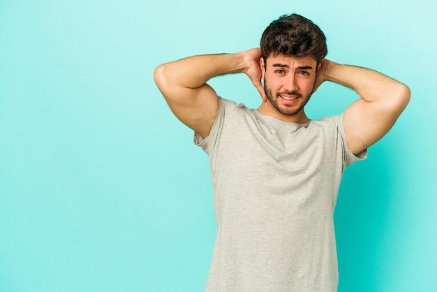 Jonge blanke man geïsoleerd op blauwe achtergrond achterhoofd aanraken, denken en een keuze maken.