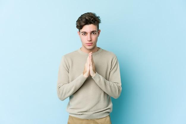 Jonge blanke man geïsoleerd op blauwe achtergrond bidden, toewijding, religieuze persoon op zoek naar goddelijke inspiratie.